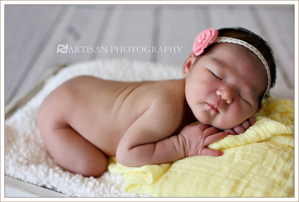 newborn baby girl picture in vintage milk crate with yellow blanket and pink flower