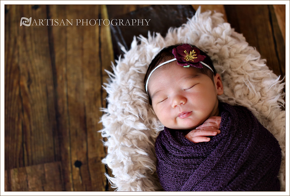 newborn baby girl picture in purple wrap and cute flower band