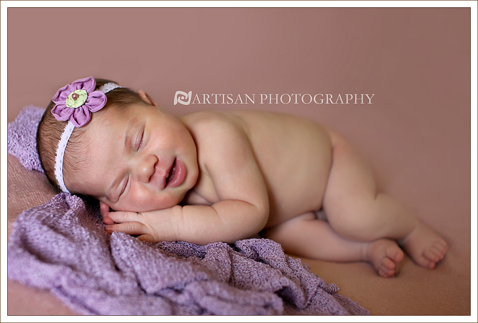 Newborn baby girl with lavender head band flower on pink blanket