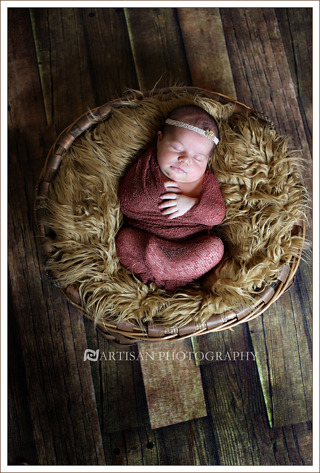 Newborn baby girl with dusty rose color wrap on fuzzy caramel blanket on a wicker basket