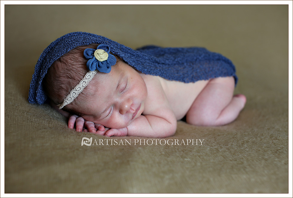 Newborn baby girl with dusty blue blanket and blue flower band