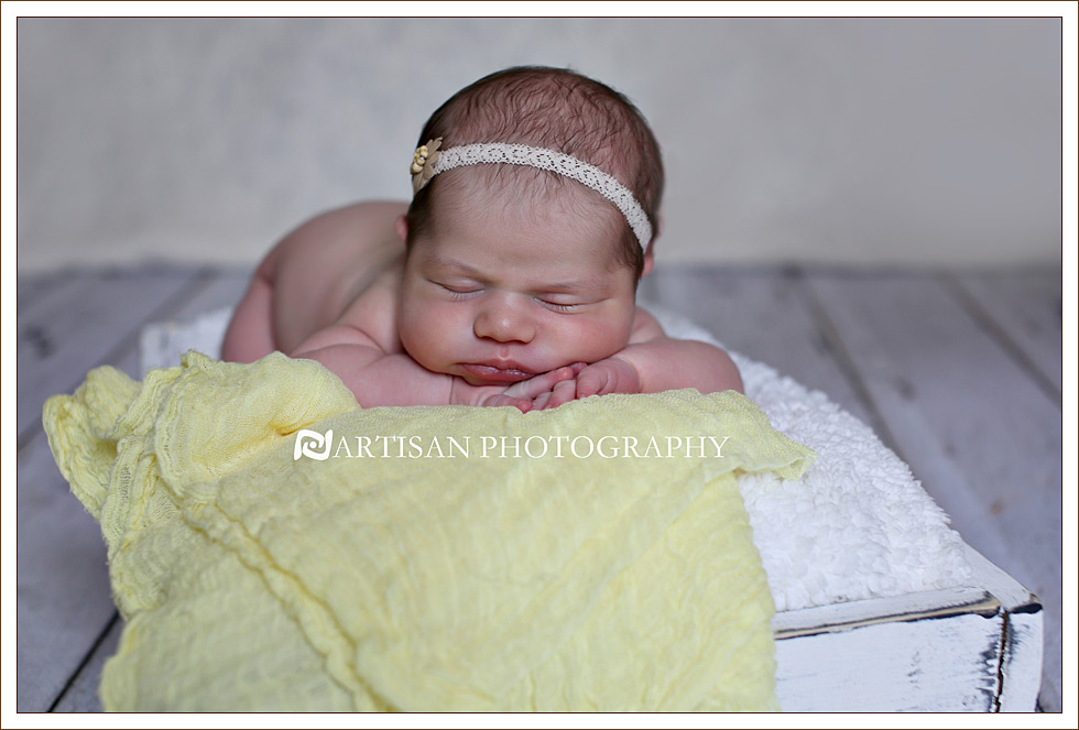 Newborn baby girl  inside a milk crate basket on white aged wood floor