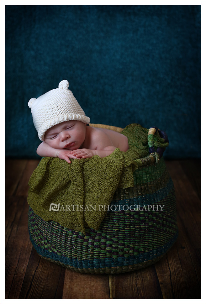 Newborn baby in blue bolga basket, with dark teal background