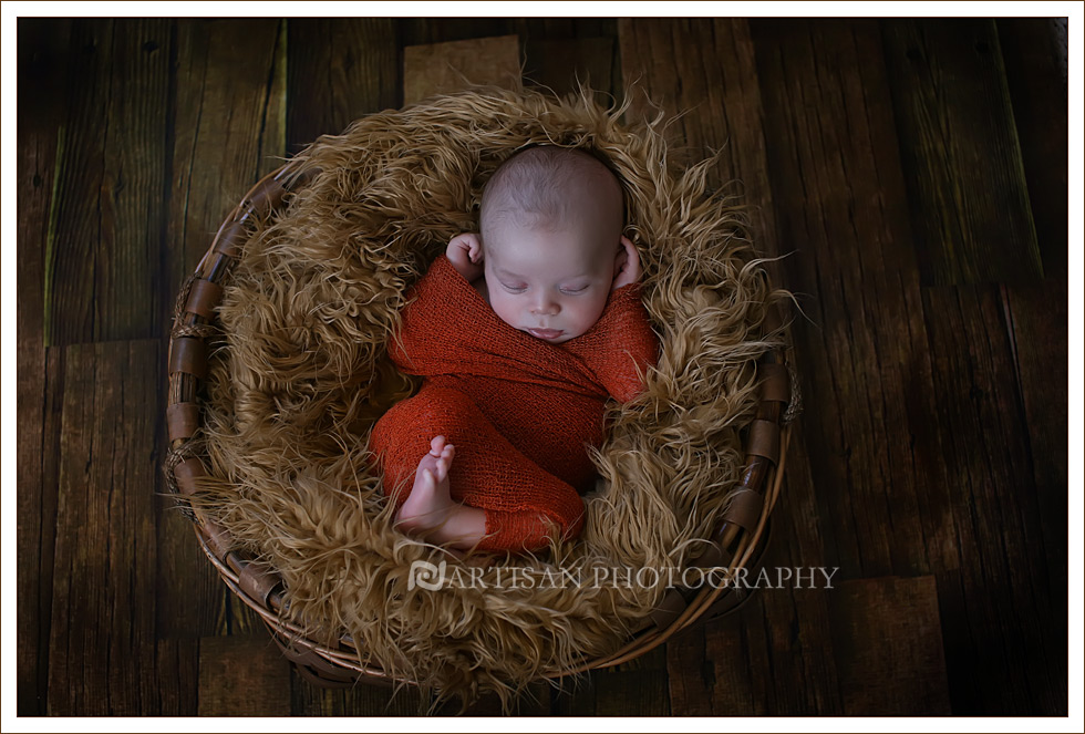 Newborn baby wrapped in an orange wrap on wood flooring