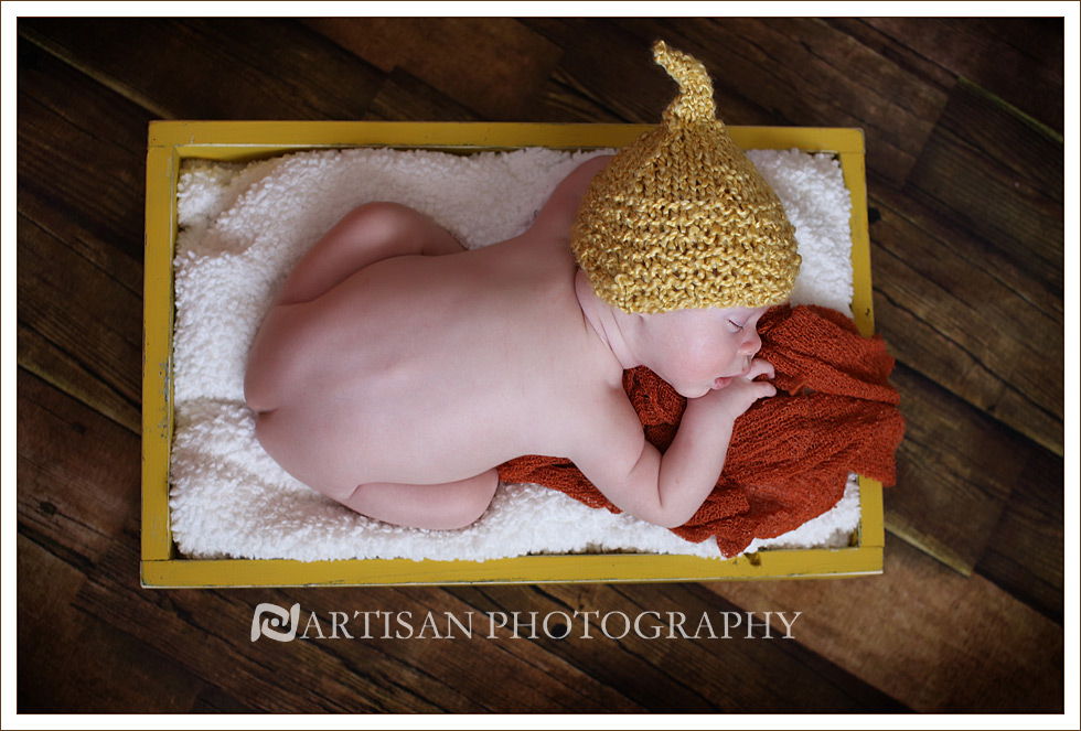 Newborn baby on yellow crate and yellow elf hat with an orange background