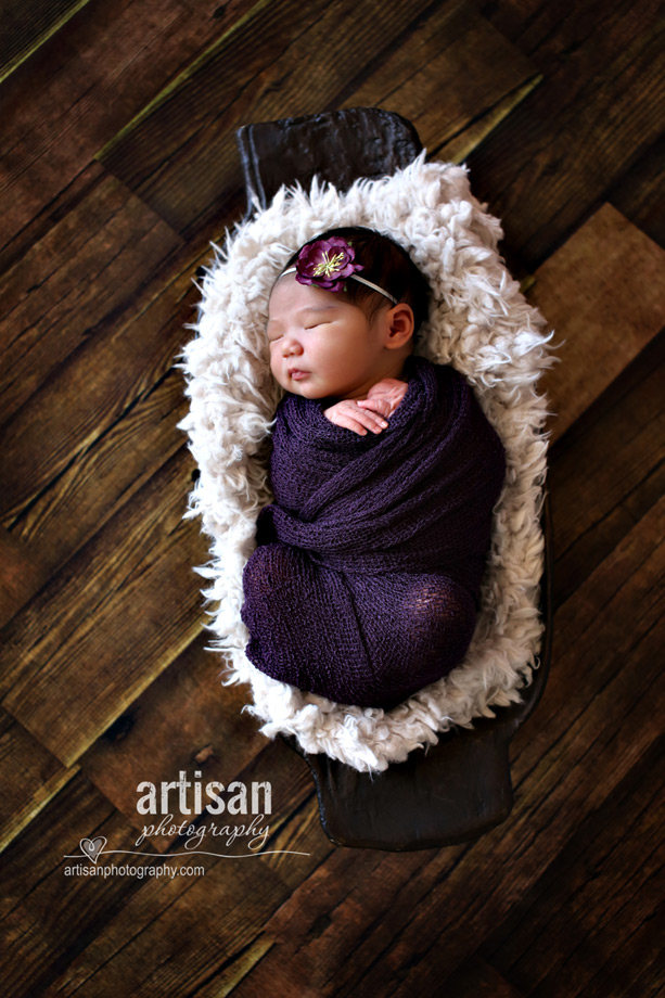 newborn baby girl in purple wrap with a purple flower on hwer hair