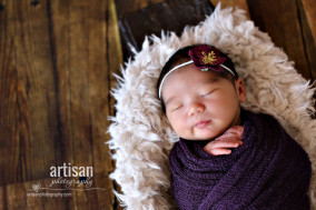 baby girl photo wrapped in purple wrap with cute flower in the hair.
