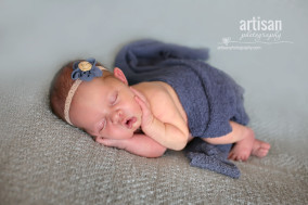 baby girl laying on blanket with flower headband and blue blanket