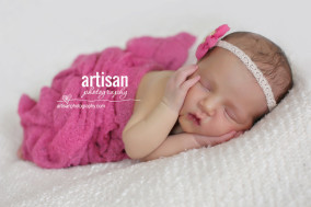 newborn baby girl photo at our Carlsbad studio in California with pink wrapp and pink flower