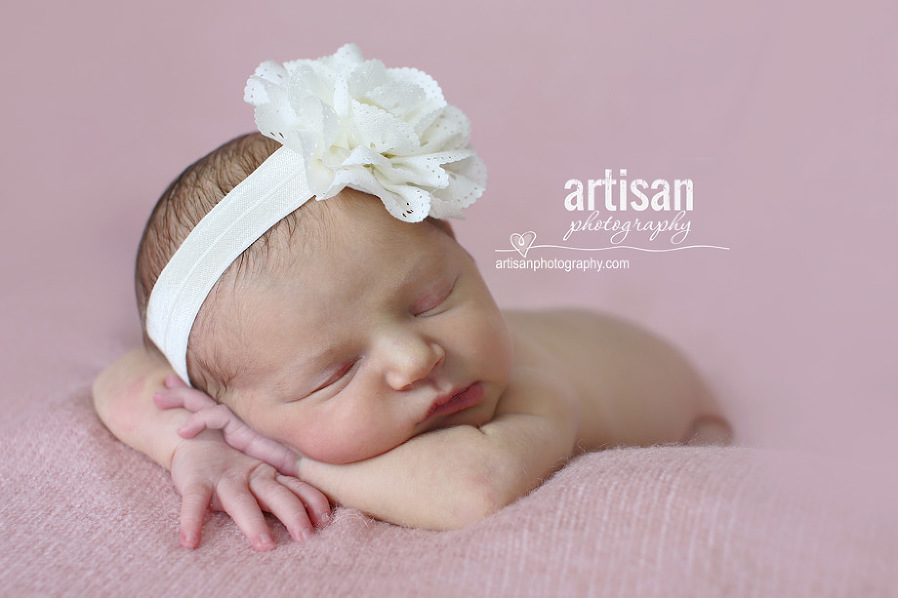 newborn baby girl photo at our Carlsbad studio in California with a big white flower band in dusty pink background