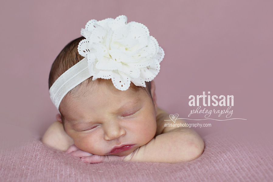 newborn baby girl photo at our Carlsbad studio in California with a big white flower band