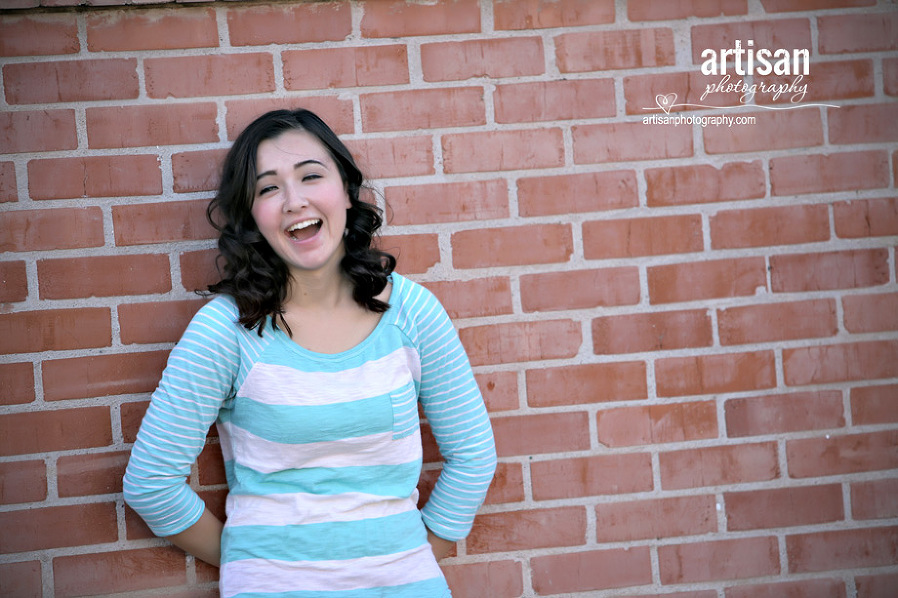 High School Senior photo of Girl leaning against a red brick wall
