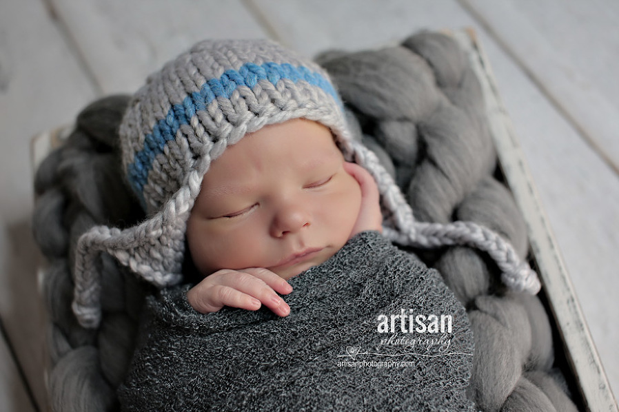 professional photo of newborn baby on grey background and a blue and grey hat