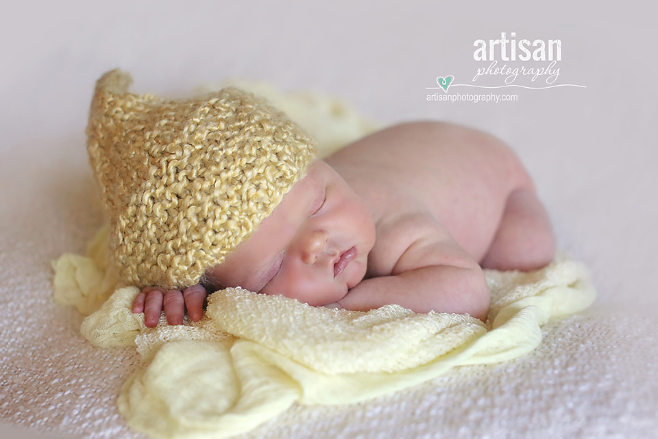 newborn baby boy laying on a cream blanket with an yellow elf hat in Carlsbad California