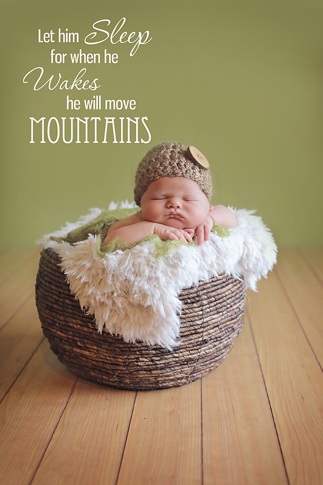 newborn baby boy laying on a brown wicker basket with a brown button hat hat in Carlsbad california