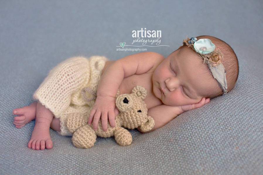 photo Newbon baby girl holding teddy bear photographed by Artisan Photography