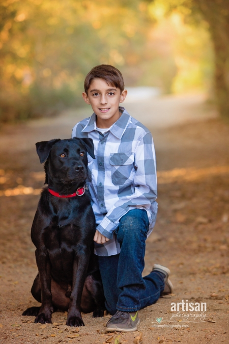 Beautiful photo out in a trail of Boy and his dog.